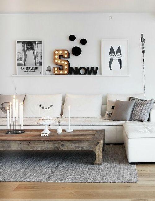 Posters em preto e branco apoiados numa prateleira única compondo uma decoração…