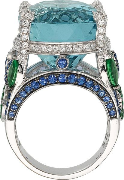 Aquamarine, Diamond, Sapphire, Tsavorite Garnet, White Gold Ring, Badgley Mischka The ring features an oval-shaped aquamarine measuring 21.17 x 16.75 x 13.56 mm and weighing approximately 26.30 carats, enhanced by full-cut diamonds weighing a total of approximately 0.45 carat, accented by round-cut sapphires weighing 1.65 carats, complemented by marquise and round-cut tsavorite garnets weighing 1.30 carats, set in 18k white gold, attributed to Badgley Mischka. Gross weight 22.90 grams. Size…