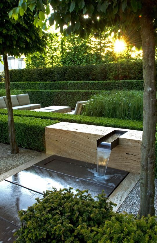 Beautiful matching of the boxwood with the stone (or wood?) water feature.