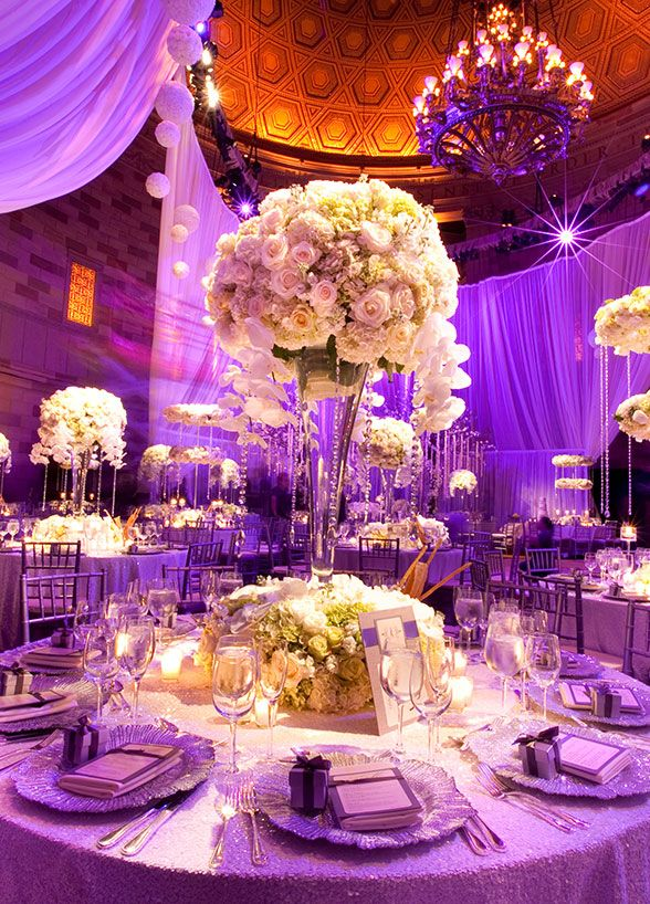A centerpiece of white roses, orchids and hydrangeas is draped in crystals. So luxurious for sparkling indoor wedding.
