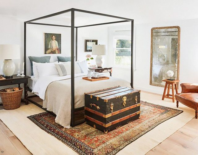 Traditional bedroom with layered vintage rugs, a canopy bed, and a vintage truck