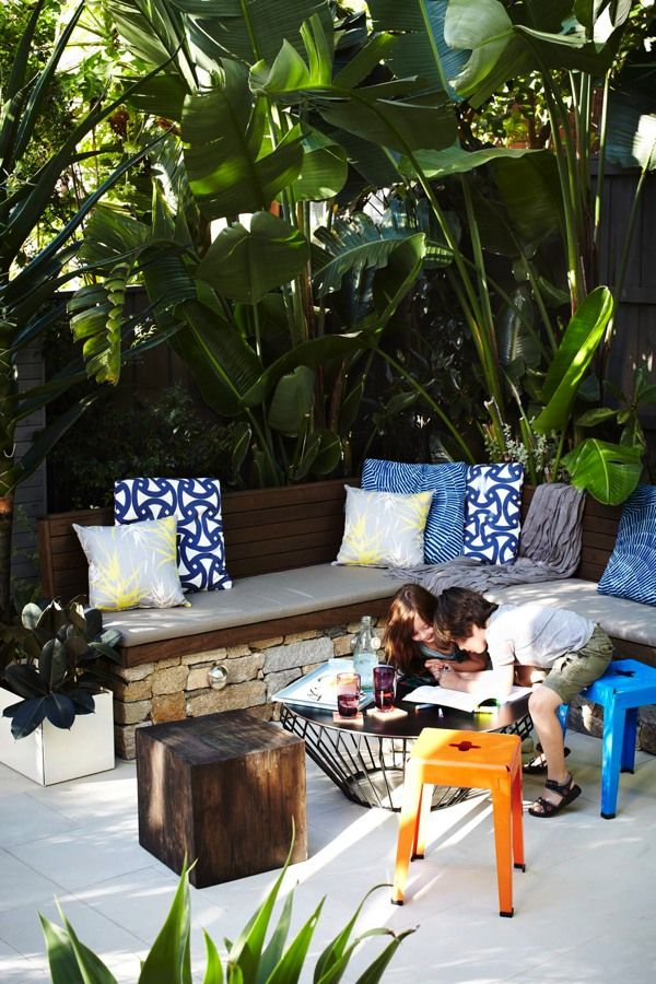 Private outdoor living rooms created with white bird of paradise, palm trees and shade loving tropical plants