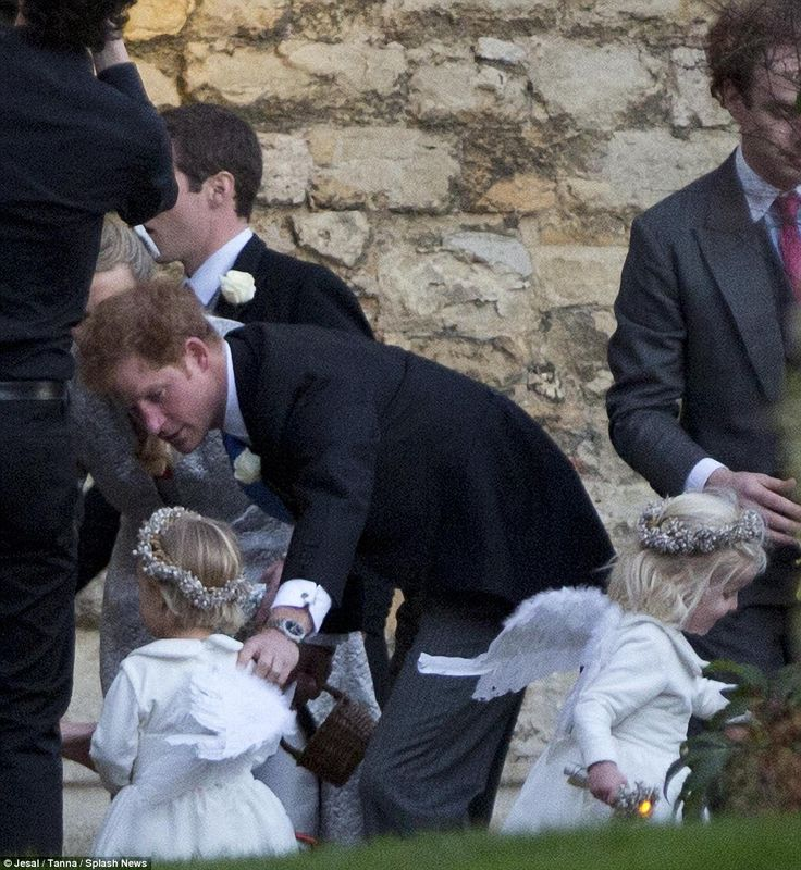 Helping out: Prince Harry helps to usher a pair of adorable little bridesmaids, both sport...