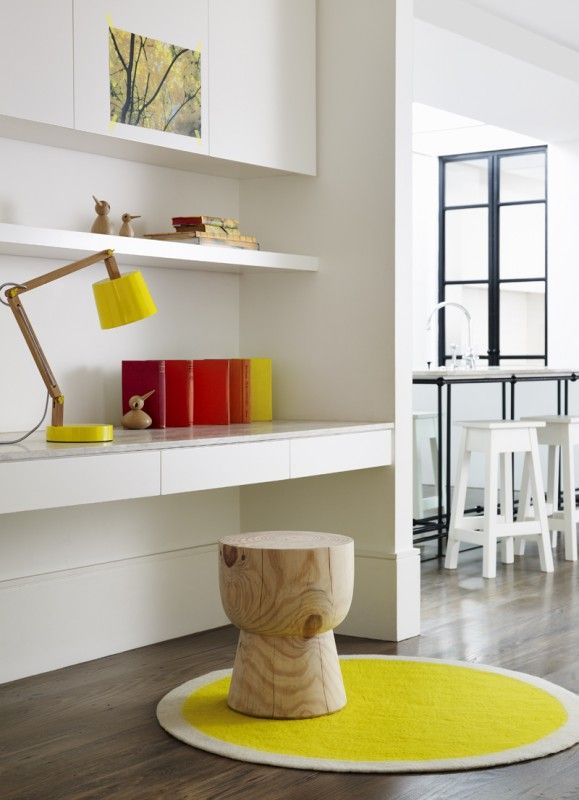 Built-in workspace/study nook near kitchen: custom joinery, white handleless cabinets, shelf, desk with stone top and handleless drawers, Mark Tuckey eggcup stool, timber floorboards, yellow circular chair mat/rug