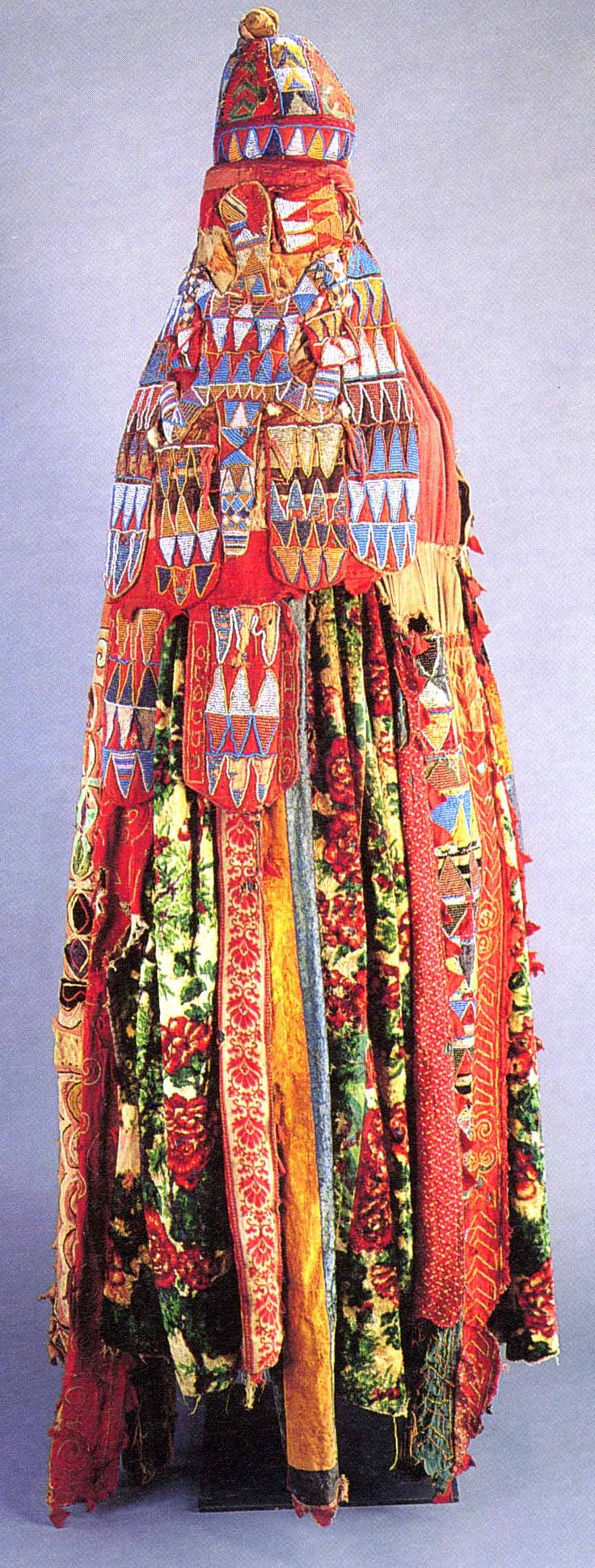 "EGUNGUN ENSEMBLE  ""Massive interlaces on beaded panels both front and back proclaim that the past, present and future are part of the infinite cycle of existence: birth, life, departure, return. They recall the whirling return of the past into the present, and simultaneously, the  spiraling outward departure on new life journeys into the future."""