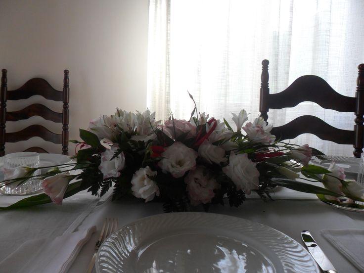Tavola all white con tovaglia bianca in cotone, piatti in porcellana bianca, posate d'argento, bicchieri in cristallo. Centrotavola: composizione con fresie e felci e roselline bianche.