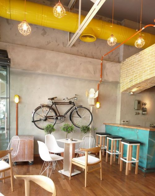 Neutral palette with pops of yellow and powder blue. Hanging bicycle is a surprisingly cool piece of wall art. (Cello cafe in Kilkis, Greece  http://www.contemporist.com/2010/07/14/the-cello-bar-by-lime-studio/)