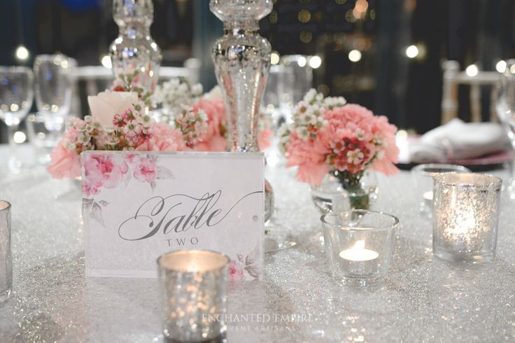 Set in a room of cascading fairylights, this romantic wedding style exuded class and elegance. An array of delicate pink hues were created throughout the centrepiece, to compliment our  wedding stationery. Complete with pink watercolour, florals, menus and table numbers complimented the silver sequin cloths and silver mercury candle holders. Limewash Tiffany chairs brought this feminine theme together by adding an earthy element. Youtube: https://www.youtube.com/watch?v=SCevKsEAy7E