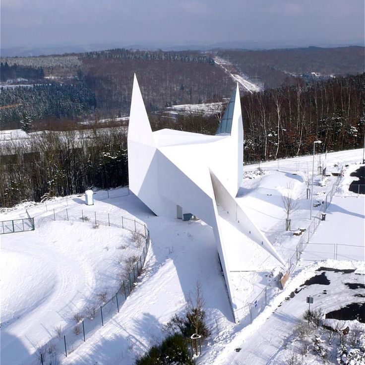 Siegerland Motorway Church by Schneider Schumacher in Wilnsdorf, Germany. Batman's dream home? A stylised white silhouette of a traditional village church representing a built version of the motorway church signage also reminiscent of Batman.