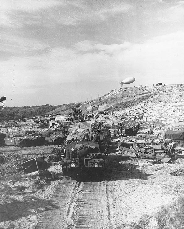 US Army vehicles moved inland from a Normandy invasion beach, Jun 1944. (US National Archives)
