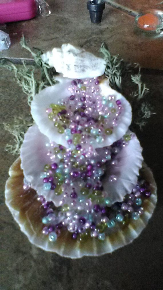 Magical Waterfall 1h 2w 2 1/2l. Shell waterfall with beads trickling down and a moss background. Choose from green or purple. Not recommend for outdoor use. Perfect for fairy gardens, doll houses, or just for decoration.