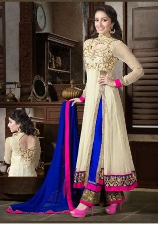 Designer Offwhite And Royal Blue Anarkali Suit:- A designer Anarkali in off white Net constructed with kalis and open slit on the sides. The yoke is finely designed and embroidered with Zari and resham with full sleeves. Bottom of the Kurta is carved from an embroidered lace border in Zari over a blue base and bright pink borders. Teamed with cigarette pants heavily ornamented at the bottom with shimmer lace and magenta embroidered lac with piping.