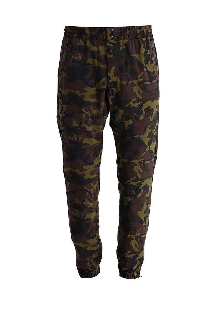Спортивные брюки Nike выполнены из нейлонового текстиля цвета хаки с камуфляжным принтом. Модель зау