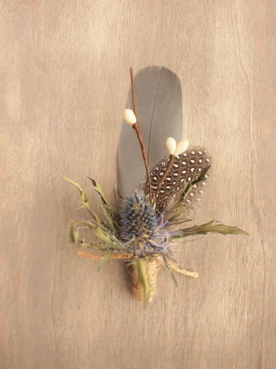 This cute little boutonniere features a dried eryngium thistle, natural grey goose and spotted guinea feather accented with Ivory millinery