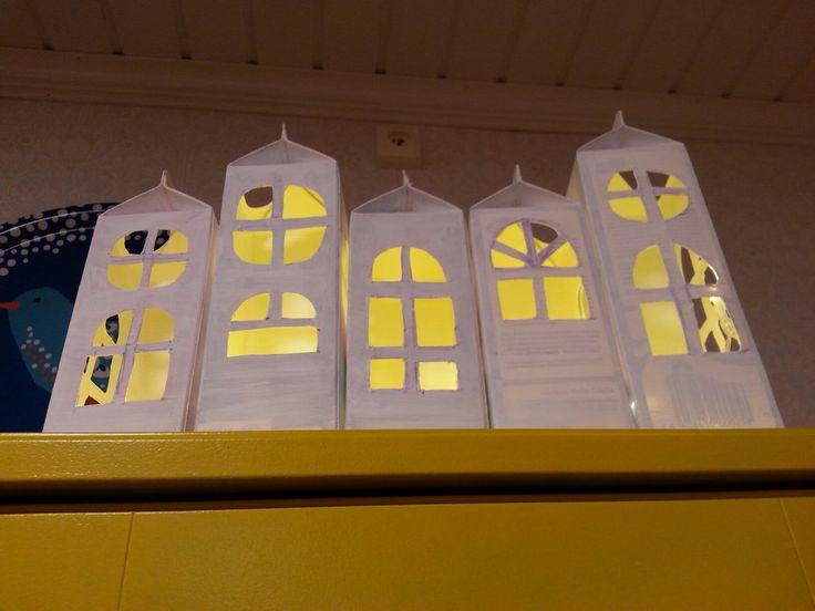 Maitopurkkitaloja, maalattu askarteluvärillä. Sisällä paristokäyttöinen valoketju.
