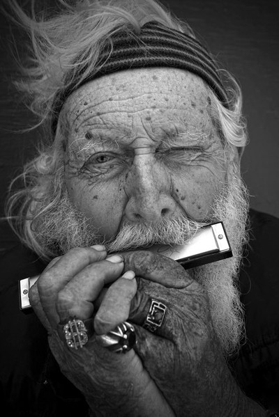 Old man playing harmonica..... His face tells such a story