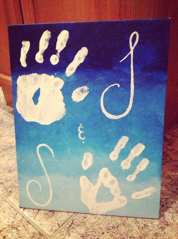 Using a canvas board, I took a damp sponge and started with a dark blue paint, mixing it with white as I worked my way down the board. I was attempting to give it an ombré look. Then my boyfriend and I painted our hands white and stamped them on the board, and I painted our first initials beside of our hands. It was really easy and a cute idea!