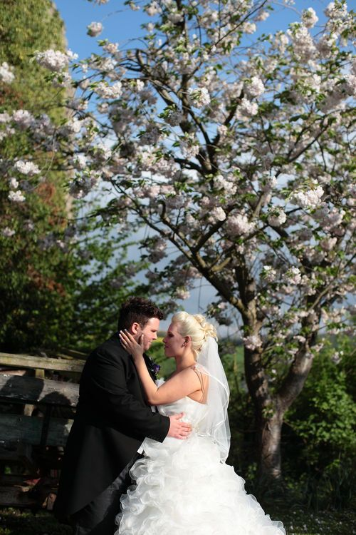 Romantic image of bride and groom kissing under tree