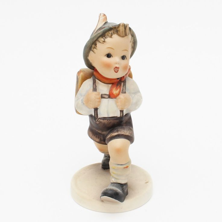 "A Hummel porcelain figurine. It is the ""_School Boy_ figurine, depicting a young boy dressed in lederhosen. He is wearing a blue cap with a red feather. He is mid stride and carrying a knapsack. The bottom is marked ""W. Germany"" with the Goebel ""baby bee"" logo in blue."