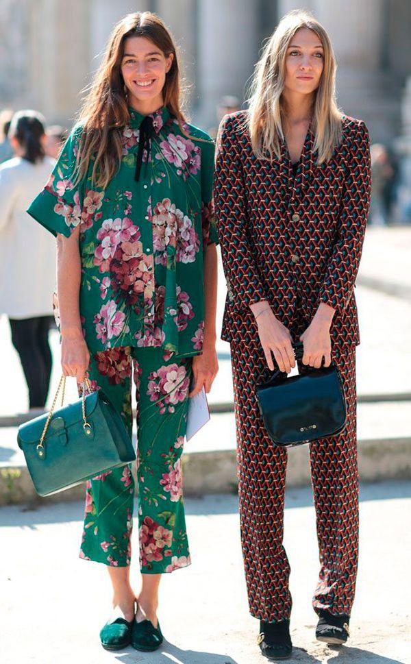 Mulheres posam para foto de street style vestindo conjuntos estilo pijama, um estampado com triângulos vinho e o outro com fundo verde e floral