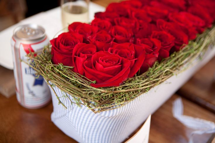 """Mossy grapevine branches are added to long custom-made seersucker trays of beautiful """"Freedom"""" red roses. Photograph by Siegel Thurston Photography http://www.storyboardwedding.com/4th-of-july-inspired-wedding-red-white-and-blue-done-to-perfection/"""