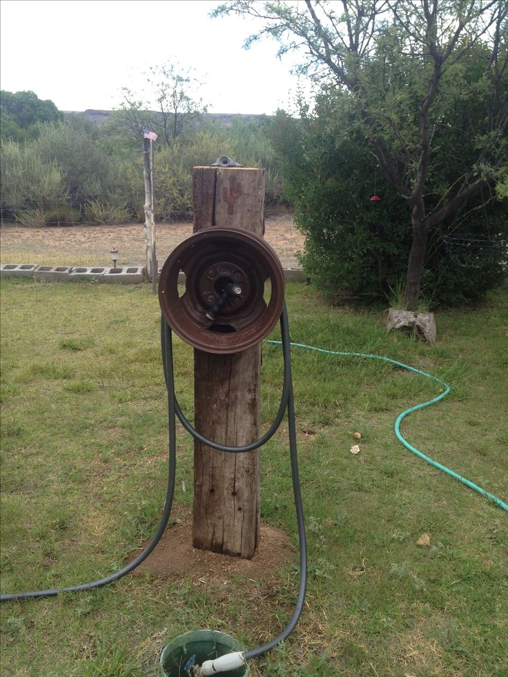 Hose reel from an old rim and railroad tie.