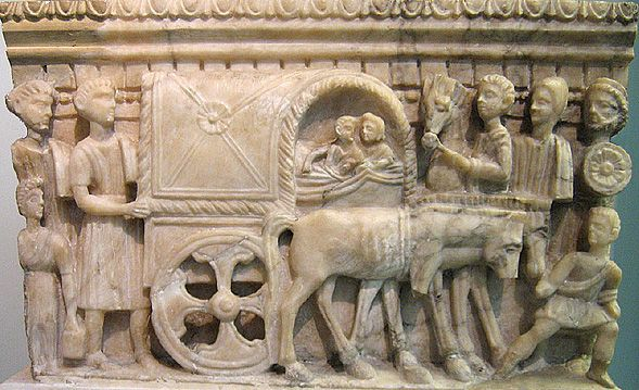Carpentum: Etruscan alabaster cinerary urn with relief on front of a couple reclining in a covered wagon (carpentum) on their way to the underworld, surrounded by mourners. From Volterra, 100-50 BCE. London, British Museum.