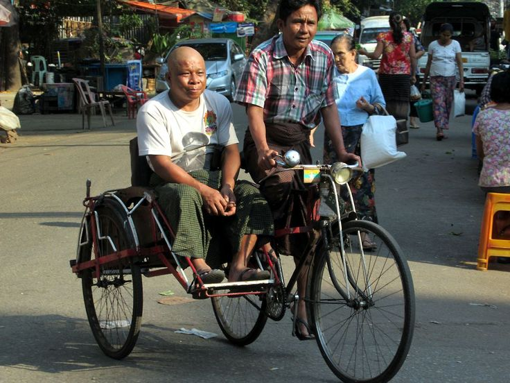 Though banned in the city center, cycle rickshaws are still a means of transportation on the back streets of Yangon, Myanmar (Burma).