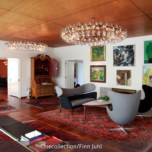 Mehrere Wandbilder aneinandergereiht verwandeln ein Wohnzimmer in eine Galerie. Die  Kronleuchter, eine mit Holz verkleidete Decke und ein dunkler Parkettboden,…