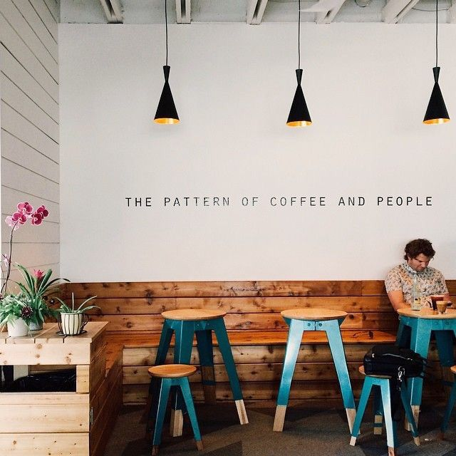 Coffee/ Retail Space Inspo - really LOVE that color wood on the benches, not a huge fan of the stools, but love the white walls and white wood wall. Love the little letters and the lights. Basically, remove the stools and ya got it.