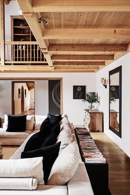 The double-height sitting room of The White Company founder's Klosters chalet is decorated in warm neutral tones to blend in with the wooden beams of the mezzanine. Black cushions and a black-framed mirror punctuate the otherwise white and grey colour scheme. The chaise longue was designed by Nicky Dobree. Living Room Design Ideas