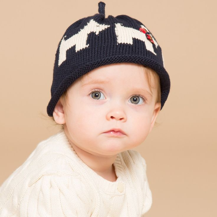 Merry Berries adorable, unisex, navy blue knitted baby hat made from soft cotton with a rolled up hem and sweet Scottie dogs featuring a little tartan bow collar. Model: Height 75cm (average 12 months) Size of hat shown in the photo: 12-24 months