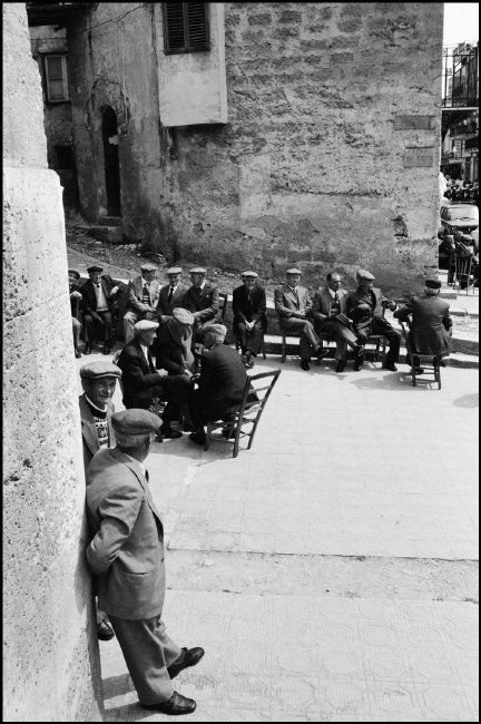 Ferdinando Scianna - Sicily, Petralia, men sitting in the street.1977.