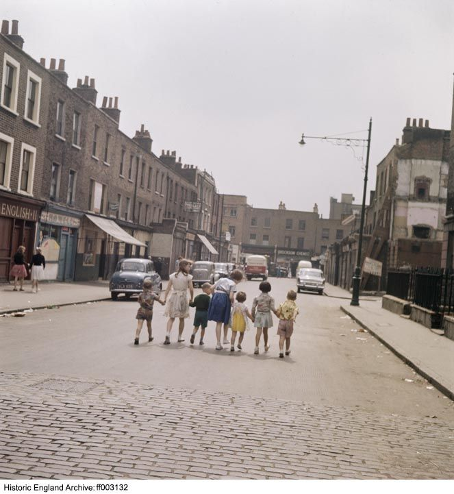 FF003132 A line of children hold hands as they walk along the middle of White Conduit Street towards the junction with Chapel Market in Islington. Much of the street was demolished in the late 20th century to make way for Tolpuddle Street and a car park. White Conduit Street, Islington, Greater London Authority, N1 1950s - 1960s. John Gay.