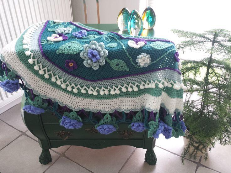 Blauwgroene tinten en paarse viooltjes op deze gehaakte omslagdoek in Ibiza Style. Geinspireerd door Pollevie en Adinda Zoutman