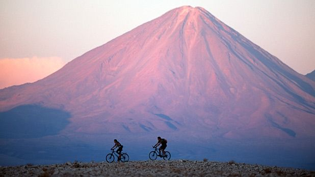 A pair of bikers pedal in the Atacama Desert against a backdrop of Volcan Licancabur.