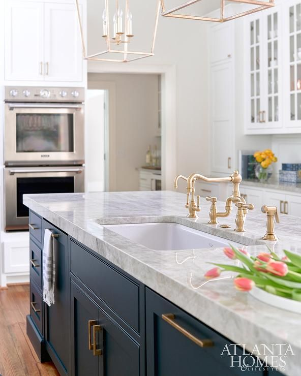A beautifully designed dark blue center island adorns brass pulls and a gray quartzite countertop fitted with a curved undermount sink paired with an antique brass faucet lit by brass  Darlana Medium Lanterns.