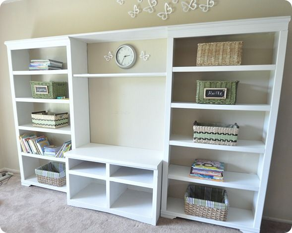 This is two bookshelves and a TV stand painted and put together to look like a built in entertainment unit. I am definitely putting this on my to-do list.