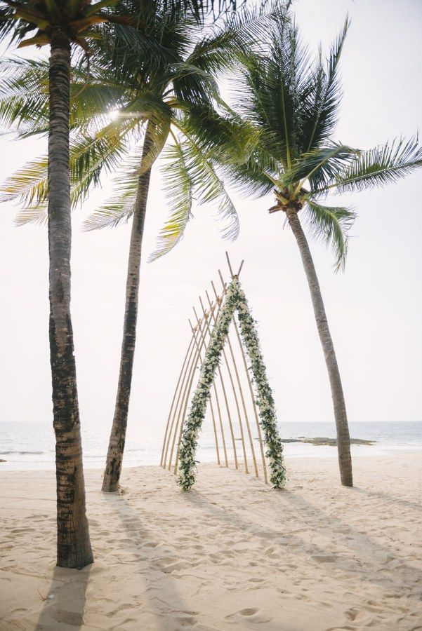 beach wedding ceremony with bamboo arch