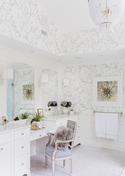 White and silver bathroom features walls clad in Schumacher Twiggy Silver Wallpaper lined with a make up vanity and a gray French chair lined with a gray Mongolian pillows flanked by his and her washstands and arched inset mirrors illuminated by Barbara Barry Simple Scallop Wall Sconces alongside a marble basket weave floor lit by a Jacqueline Chandelier.