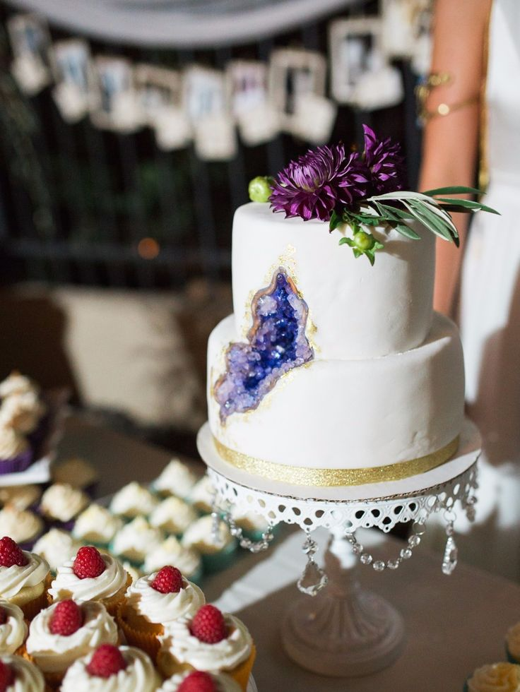geode wedding cake with purple floral topper// opulent treasures white chandelier cake stand