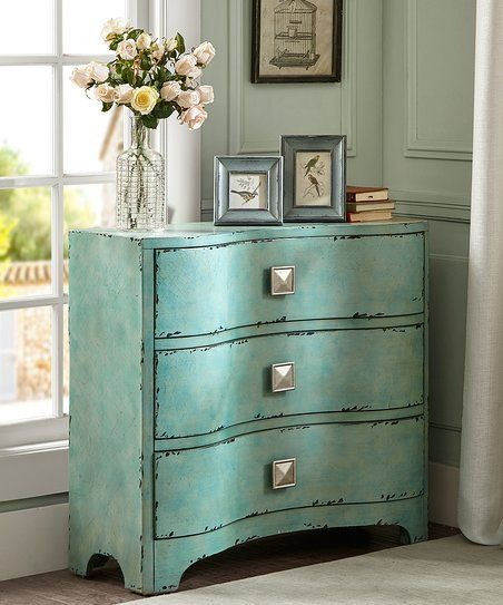 Boasting a distressed blue finish and contemporary shape, this chest enhances home décor with a pop of style.