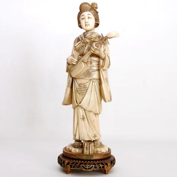 Escultura em marfim oriental representando Gueixa com instrumento musical, apoiada sobre base de m