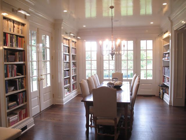 Love this cozy dining room lined with bookcases. Glossy ceiling, windows, doors, sconces.