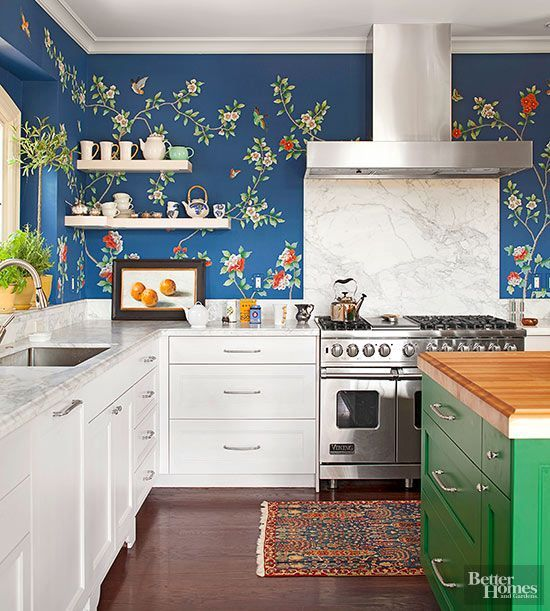 Go bold with an all-over wallpaper treatment that blooms with a garden motif. Traditional white cabinetry, marble countertops, and open upper shelves prevent the bright blue backdrop from overwhelming visitors. A painted green island and fun fruit artwork pick up the colors of the floral pattern./