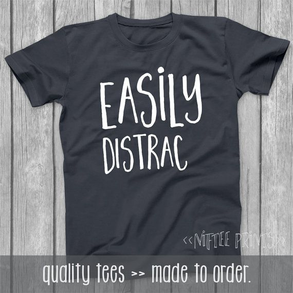 Easily Distrac - This self-explanatory, funny tshirt makes a great gift for anyone who has a sense of humor -- excellent graduation, Christmas gift, too!    I T E M . I N F O R M A T I O N ••••••••••••••••••••••••••••••••••••••••••••••••••••••••••••• Item No. NPT011   ■ Our Basic Tees are 100% pre-shrunk cotton.  ■ Our Premium Tees are fitted, 100% ringspun cotton -- soft and comfortable!  ■ Tees are short sleeve/crew neck.    See image above for size and color information.    Thank you ...