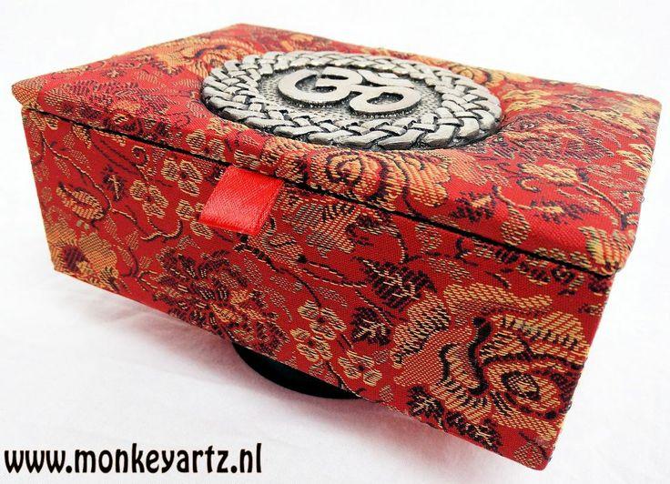 Houten met stof bekleed tarot/sieraden kistje. Metalen Ohm symbool op deksel aangebracht. Meer info: www.monkeyartz.nl