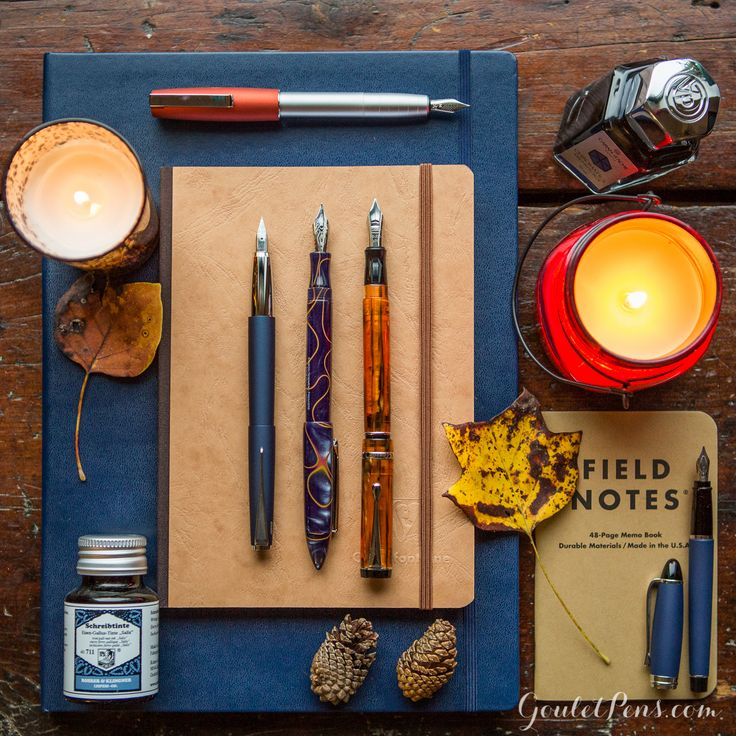 An autumn inspired flat lay of fountain pens, notebooks, and ink, with navy blues, browns, and yellows.