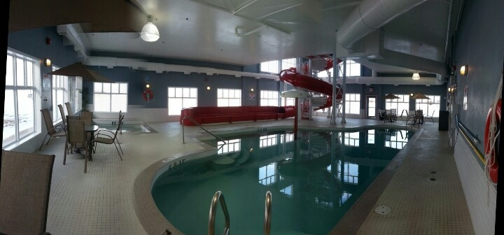 Panorama view of the swimming pool area, showing the hot tub on the left, the waterslide in the back in the pool in the front.