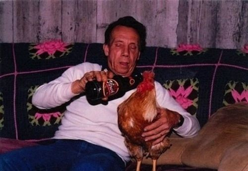 This guy giving his rooster a swig. | The 49 Most WTF Pictures Of People Posing WithAnimals